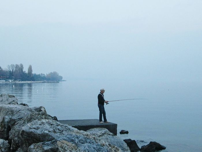 Side view of man fishing in lake against sky
