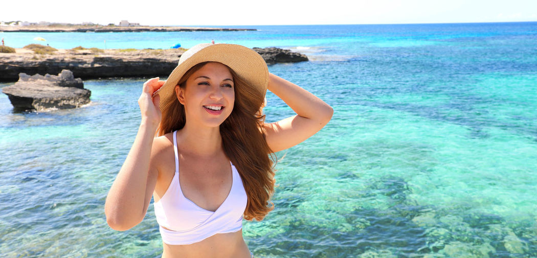 Young woman wearing hat standing at beach
