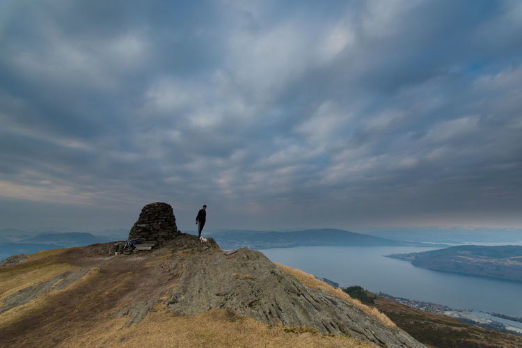 Man Standing On Mountain Against Lake