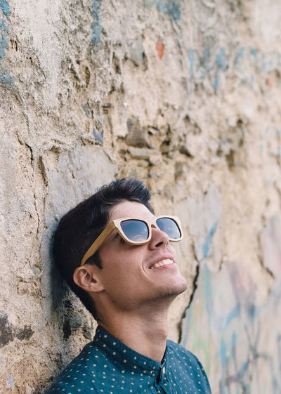 Portrait of smiling man wearing sunglasses against wall