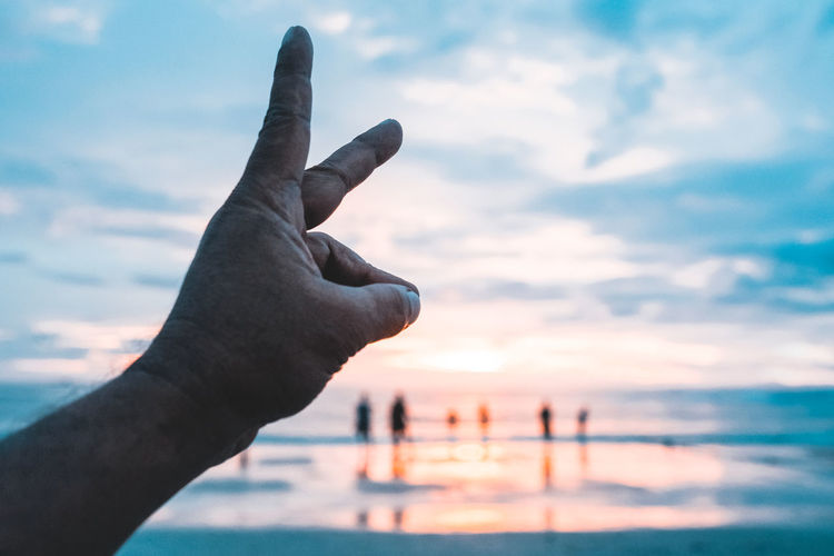 Cropped image of person hand gesturing against sky during sunset