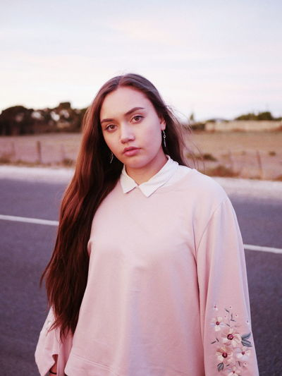 EyeEmNewHere Friends Sunset Wonderful VSCO Vscocam Composition Pink Pink Sky Dusk Soft Dusk Sky Brown Hair Road Roadsidephotography Grass Light And Shadow Light Grain Brown Eyes Feminine  Pretty Portrait Young Women Standing Beautiful Woman Looking At Camera Women Front View