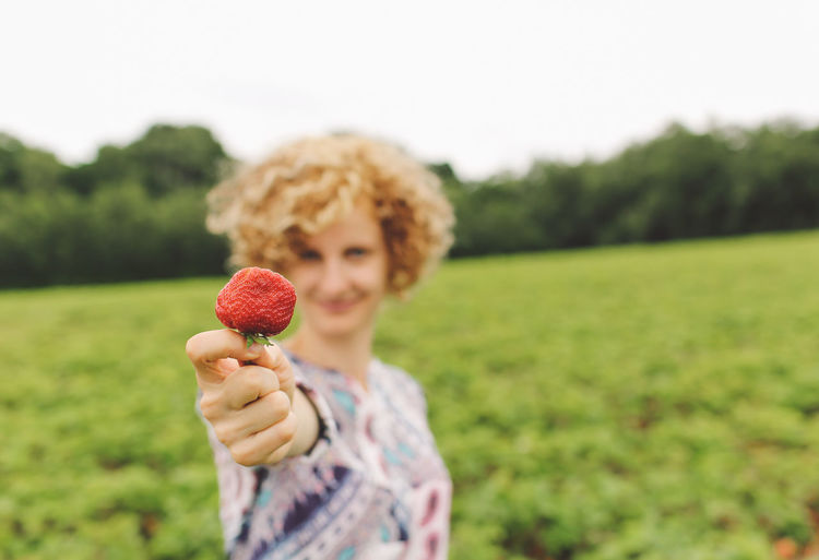 Casual Clothing Close-up Curly Hair Cute Day Farm Field Focus On Foreground Girl Grass Grassy Green Color Growth Harvest Holding Landscape Leisure Activity Lifestyles Nature Outdoors Pick Your Own Fruit Sky Smiling Strawberries Strawberry Connected By Travel 50 Ways Of Seeing: Gratitude