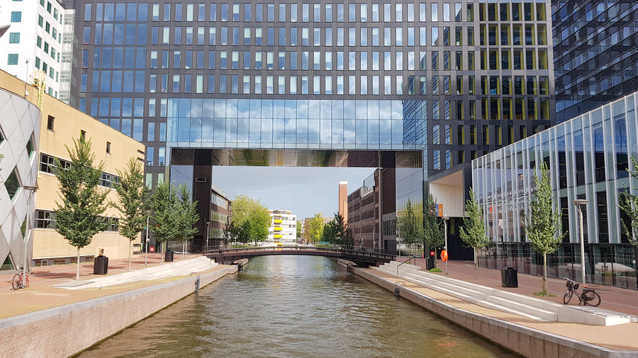 Canal amidst modern buildings in city