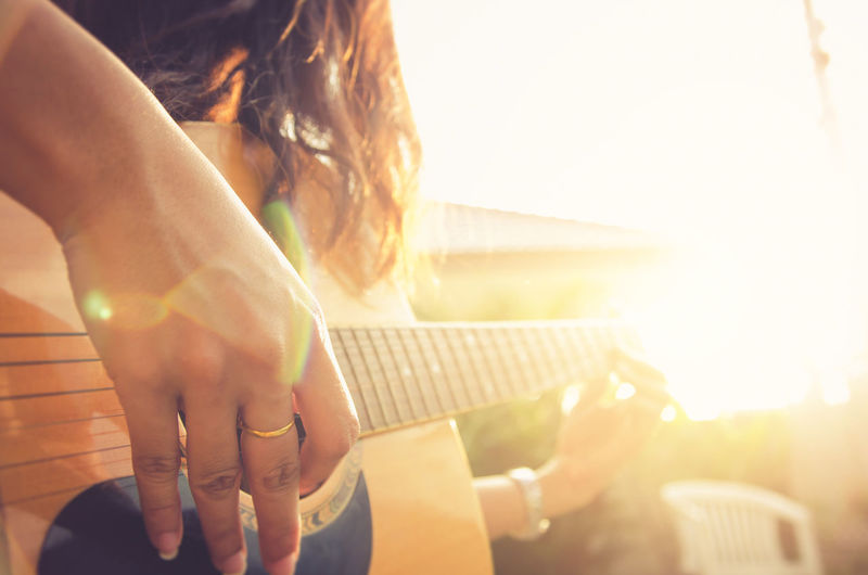 Midsection of woman playing guitar on sunny day