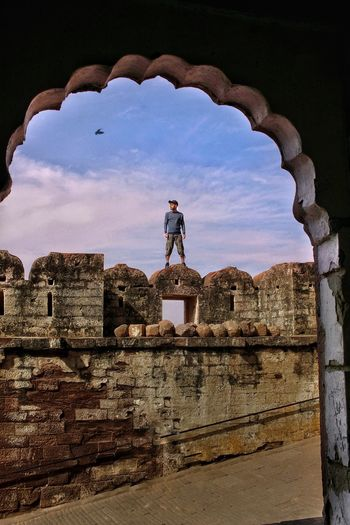 Low angle view of man standing at fort against sky