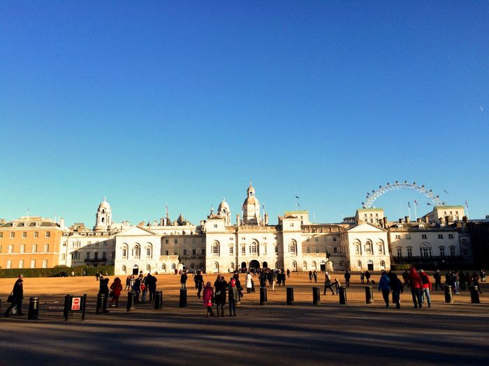 People walking by historic building against clear blue sky at st james park