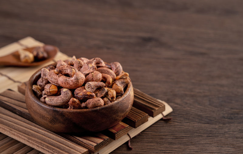 Cashew nuts with peel in a wooden bowl on wooden tray and table background, healthy raw food plate.