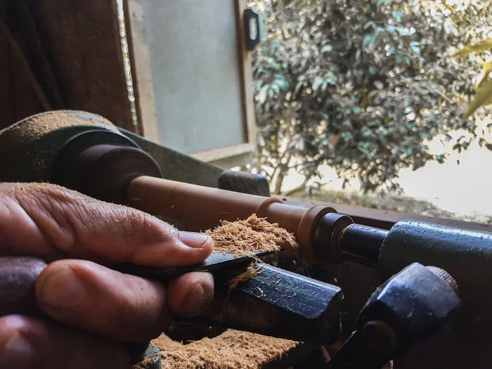 Cropped hand of man carving wood in workshop