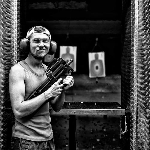 Portrait of young man holding gun while standing at target shooting range