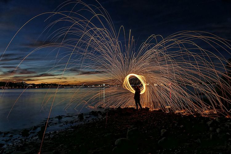 Person spinning wire wool on beach at night