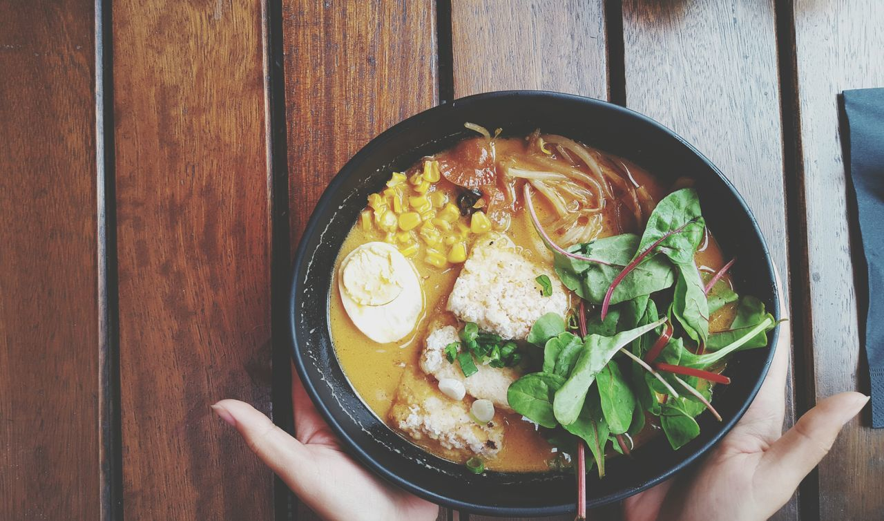 Cropped Hands Holding Food In Bowl At Wooden Table