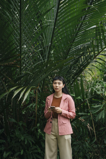 Young woman using mobile phone while standing by plant