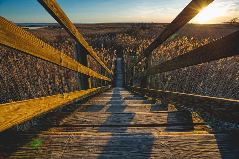 Footpath leading to bridge against sky