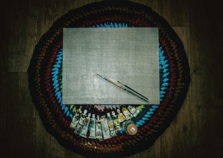 High angle view of paintbrushes and canvas on place mat
