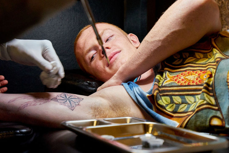 Cropped Hands Of Artist Bamboo Tattooing On Young Man Arm