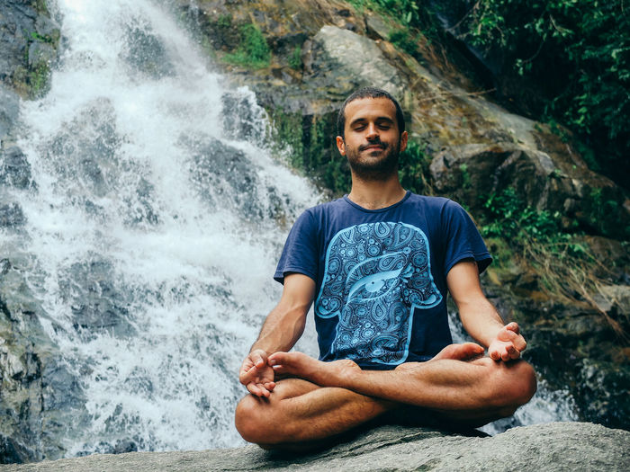 Portrait Of Man Meditating By Waterfall