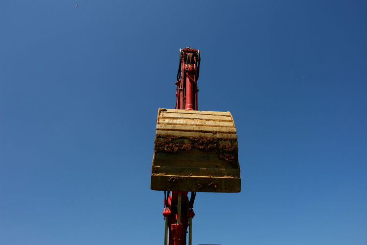 Low Angle View Of Earth Mover Against Clear Blue Sky