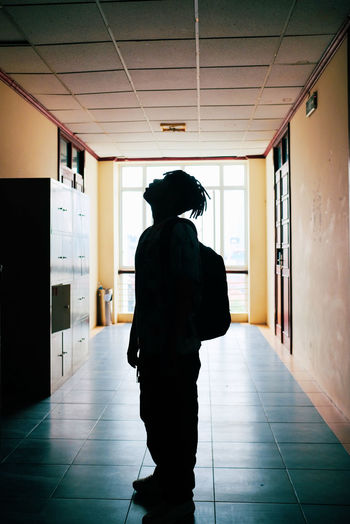 Rear view of silhouette woman standing in corridor of building
