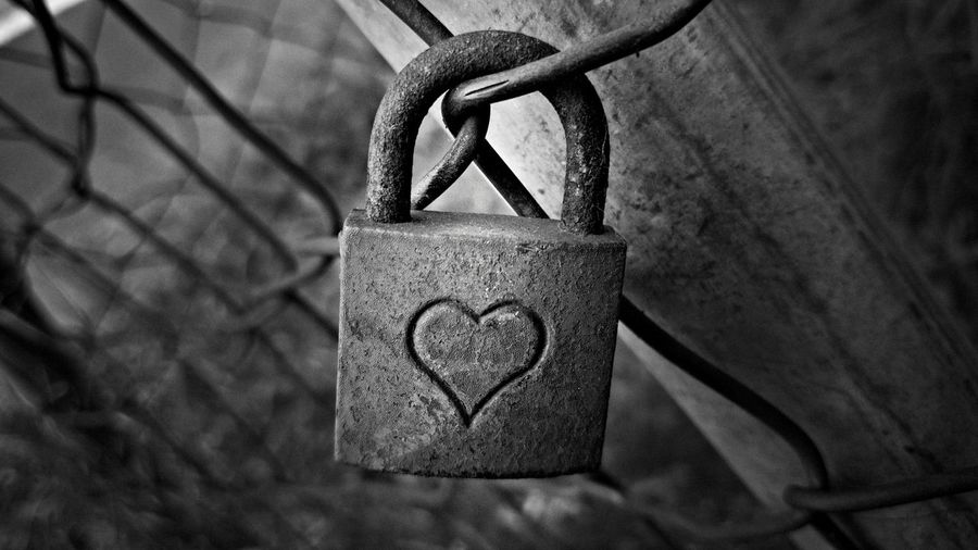 Close-up of love padlock hanging on fence