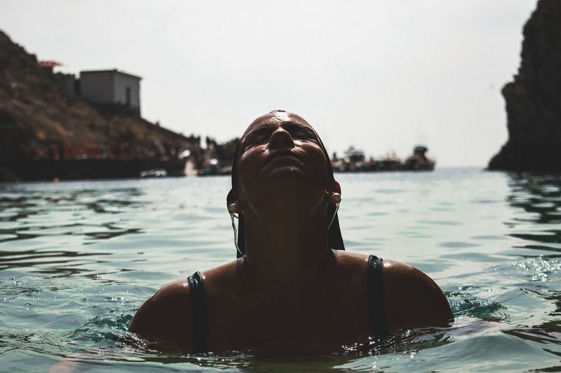 Woman Swimming In Lake Against Sky During Sunny Day