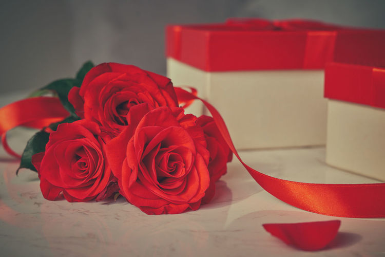Close-up of red roses by gift box on table