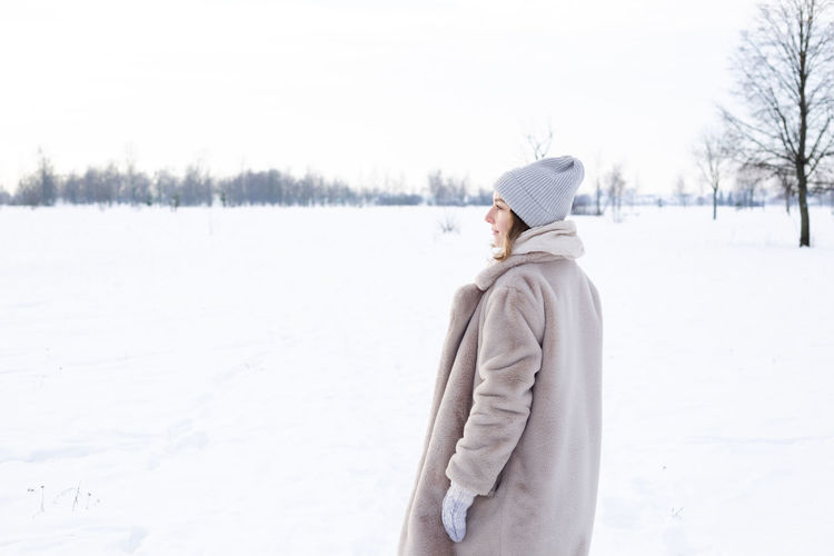Side view of woman standing on snow covered land