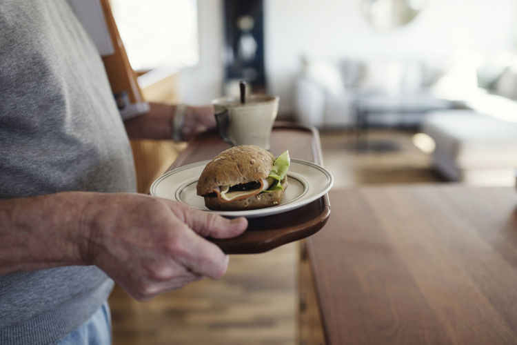 Midsection of man holding food on table