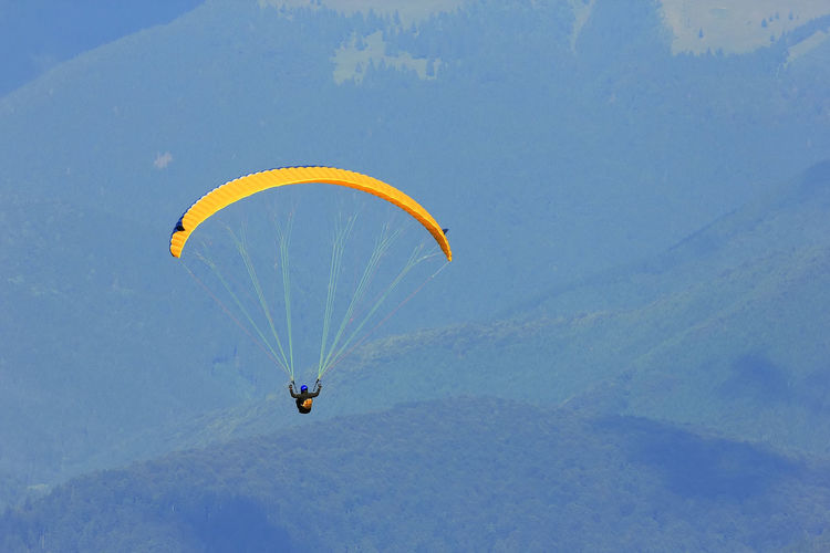 High angle view of man paragliding above mountains