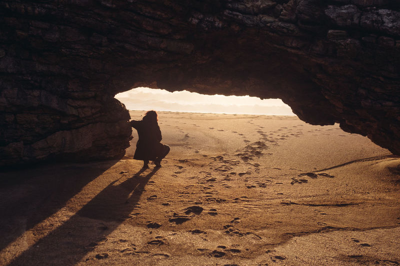 Nazaré  Beauty In Nature Cave Climbing Day Full Length Leisure Activity Lifestyles Nature One Person Outdoors People Praia Do Norte Real People Rock - Object Rock Formation Rocks Shadow Silhouette Standing Sunlight Sunset Walking Women