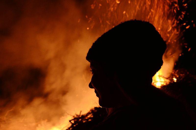 Woman Looking At Campfire At Night