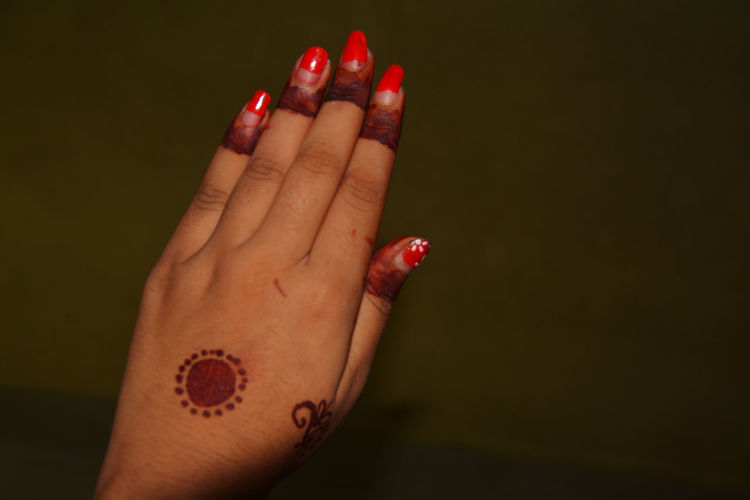 Close-up of woman hand with henna tattoo against colored background