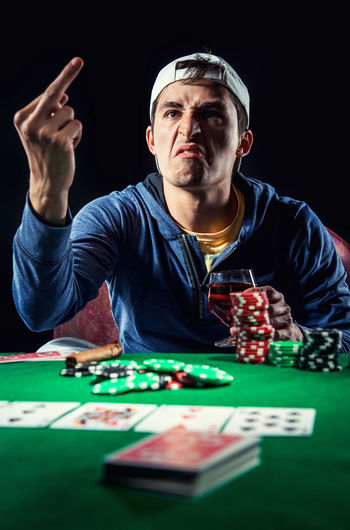 Young Man Showing Obscene Gesture While Playing Poker Against Black Background