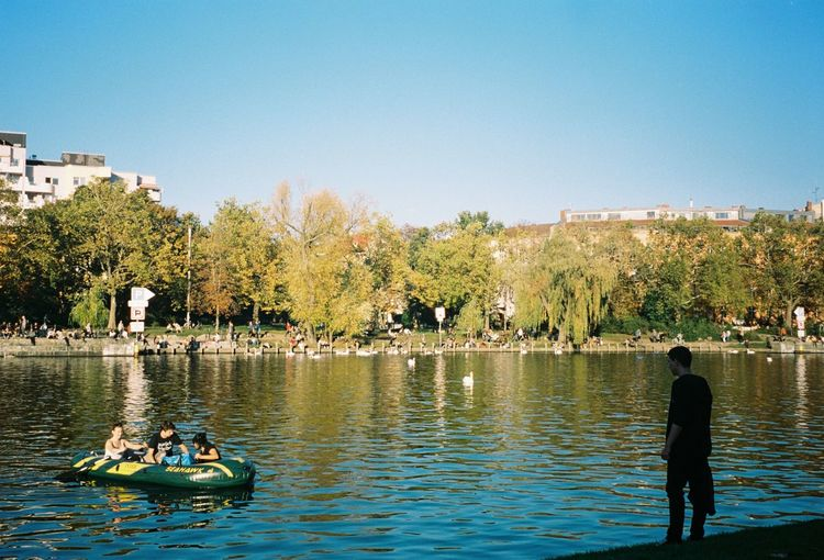 Rear view of people in river against clear sky