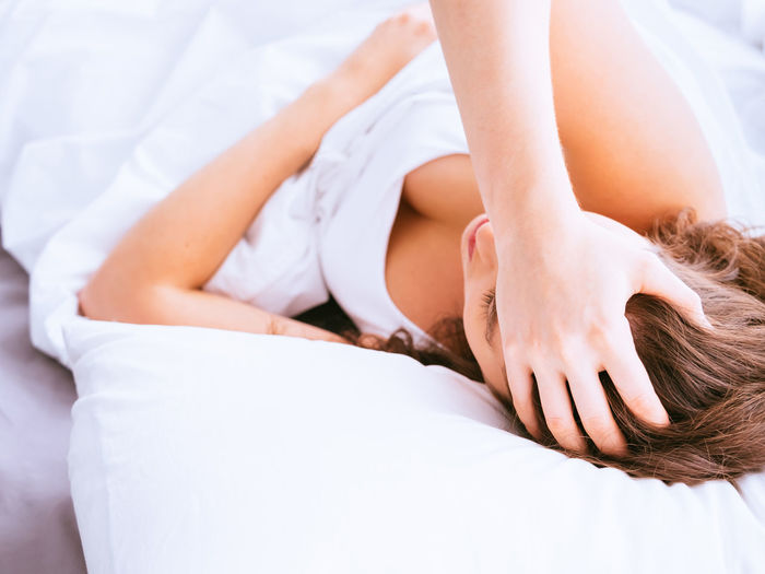 Woman with headache lying on bed at home