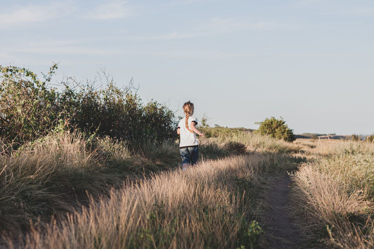 Adorable little girl running down the hill back view. happy child in wild grass countryside.