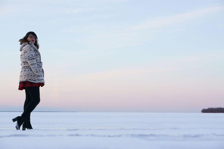 Side view of transgender male walking on snowfield against sky during sunset