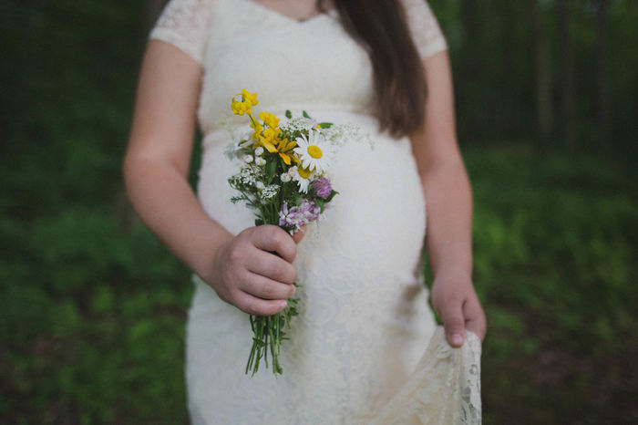 Pregnant woman wearing lace dress holding a bouquet of wildflowers in forest Anticipation Beautiful Bouquet Day Flower Lace Dress Mom To Be Mother To Be Outdoors Pregnant