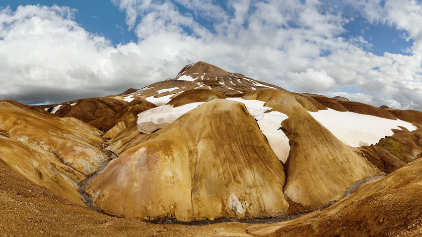 Panoramic view of a landscape in ocher and brown tones with snowfields and a small river - Location: Iceland, Highlands, area 'Kerlingarfjöll' Creekside Hiking Hills Ice Iceland Natural Colours Nature Panorama Remaining Snow Adventure Beauty In Nature Blue Sky Brown Color Clouds And Sky Hillside Landscape Mountain Range No People Ocher Color Orange Color River Scenic Landscapes Snow Fields Volcanic Landscape Wide Angle
