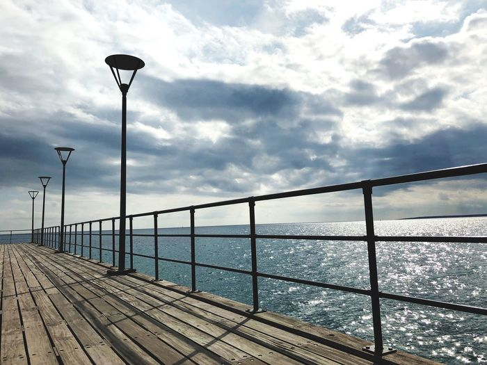 Sunlight Waves Sea Shapes Lines Wharf Clouds Art Beauty Pier Sky Street Light Water Cloud - Sky Sea Street Lighting Equipment Railing Beauty In Nature Scenics - Nature Tranquil Scene Tranquility Outdoors Architecture Sunlight Built Structure Nature No People Day Horizon Over Water