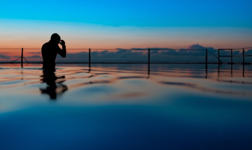 Silhouette man in swimming pool against sea during sunset