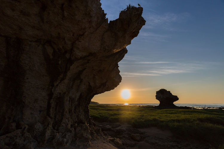 Scenic view of rock formation amidst sea against sky during sunset