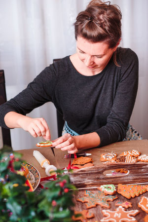 Woman decorating baked Christmas gingerbread cookies with frosting Baked Baking Biscuit Celebrating Celebration Christmas Cookie Cookies Decorated Decoration Food Frosting Gingerbread Holiday Home Homemade Icing Person Preparation  Preparing Sugar Sweet Tradition Traditional Woman
