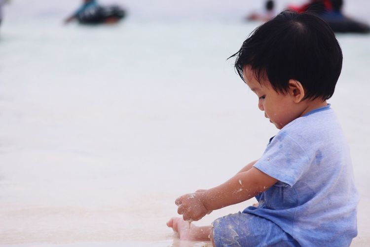 Baby boy playing with sand at beach