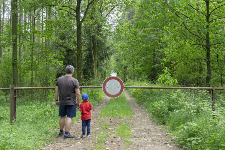 Rear view of father and son standing on footpath at forest