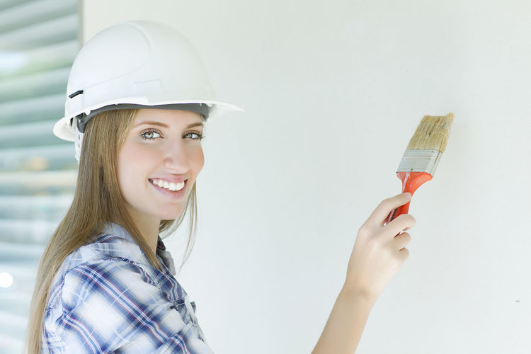 Portrait of confident female painter painting wall