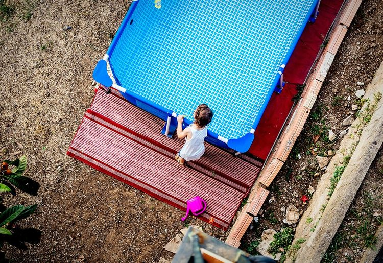 High Angle View Of Baby Playing With Wading Pool In Yard
