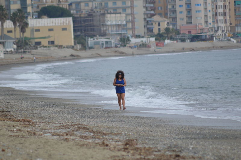 Full length of man standing on beach in city