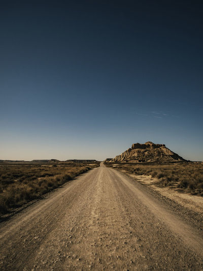 Dirt road amidst desert against clear sky