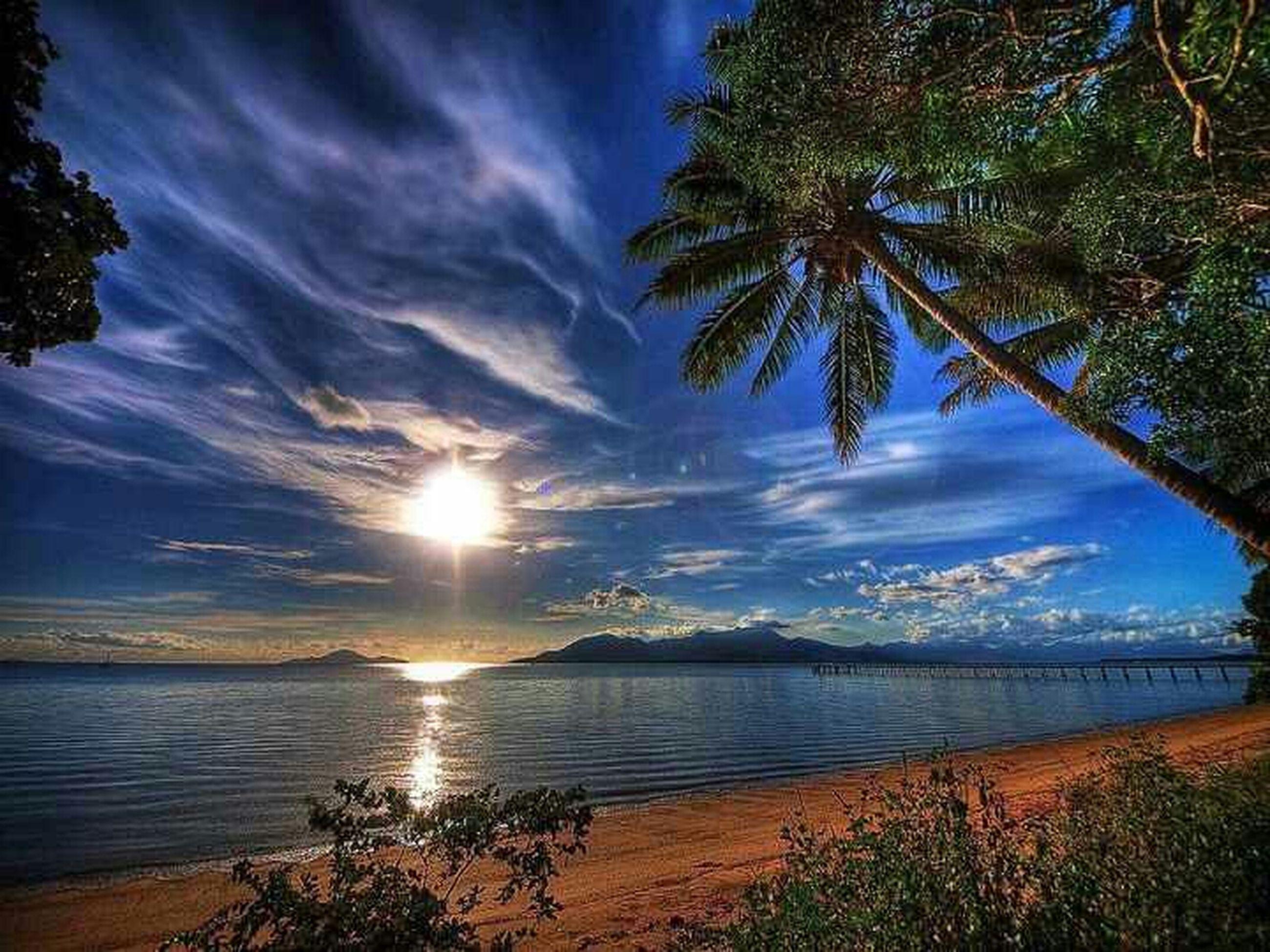 tranquil scene, tranquility, scenics, sky, water, beauty in nature, sea, tree, beach, nature, cloud - sky, sun, horizon over water, sunlight, palm tree, idyllic, shore, sunbeam, cloud, sunset